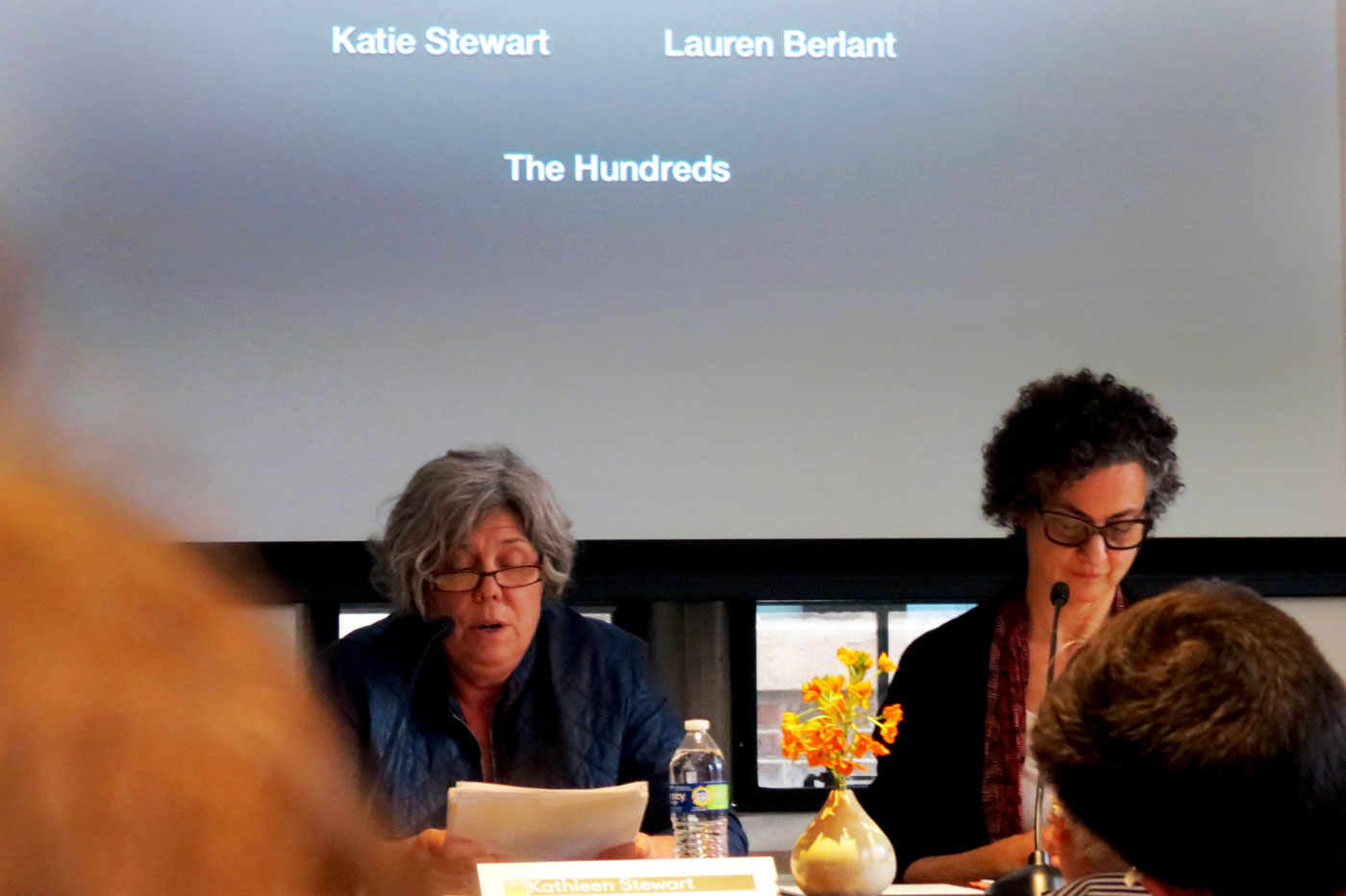 two people sit at a table speaking with presentation projected behind them