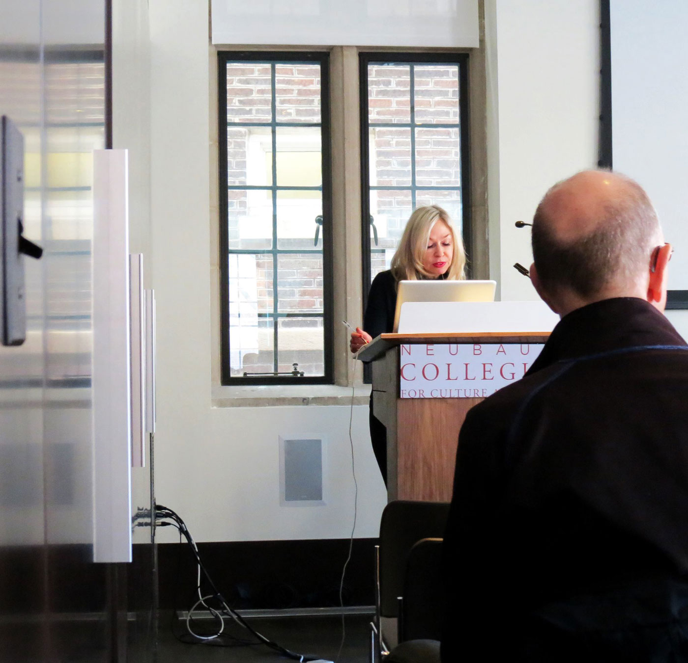 person speaks at a lectern as others look on
