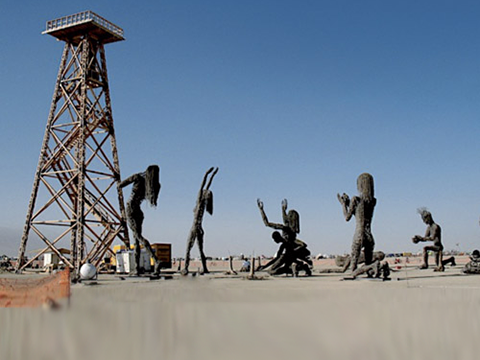 photo of four dark metal statues of naked figures worshiping a disused oil derrick in a dry dirt field