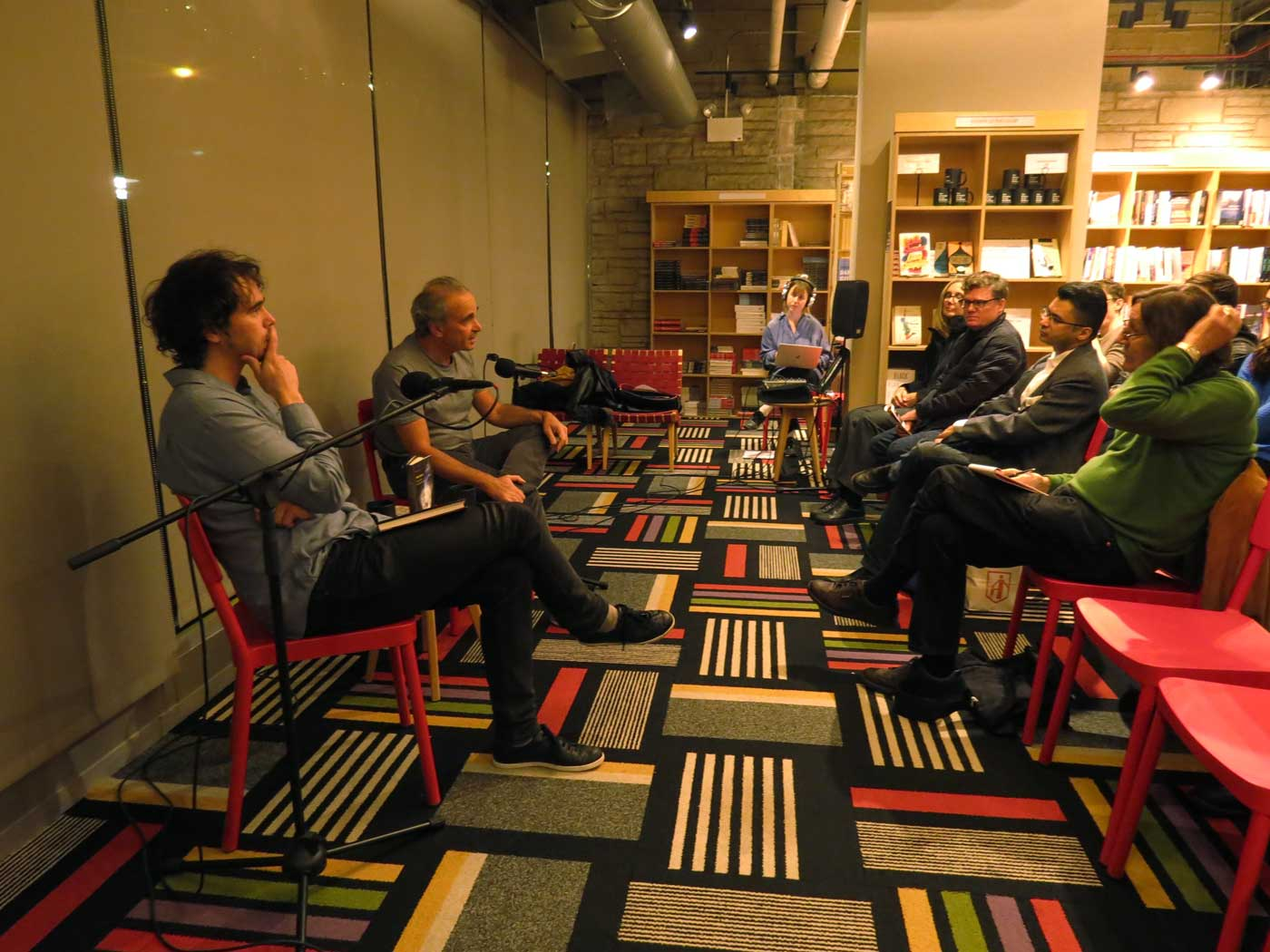 Author Michael Feher and panelist Jonathan Levy sit addressing a seated audience