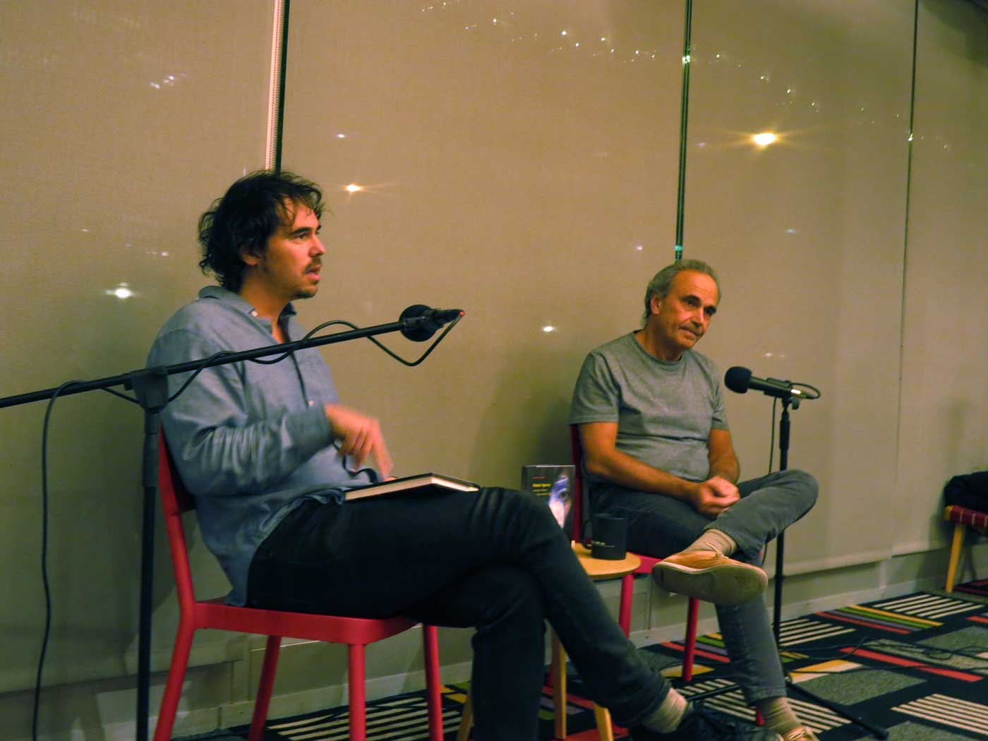 Author Michael Feher and Johnathan Levy sit addressing an audience