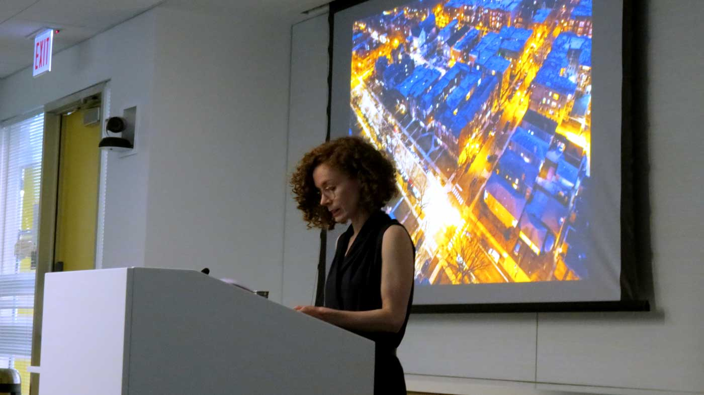 A presenter stands at a podium with an image projected behind them