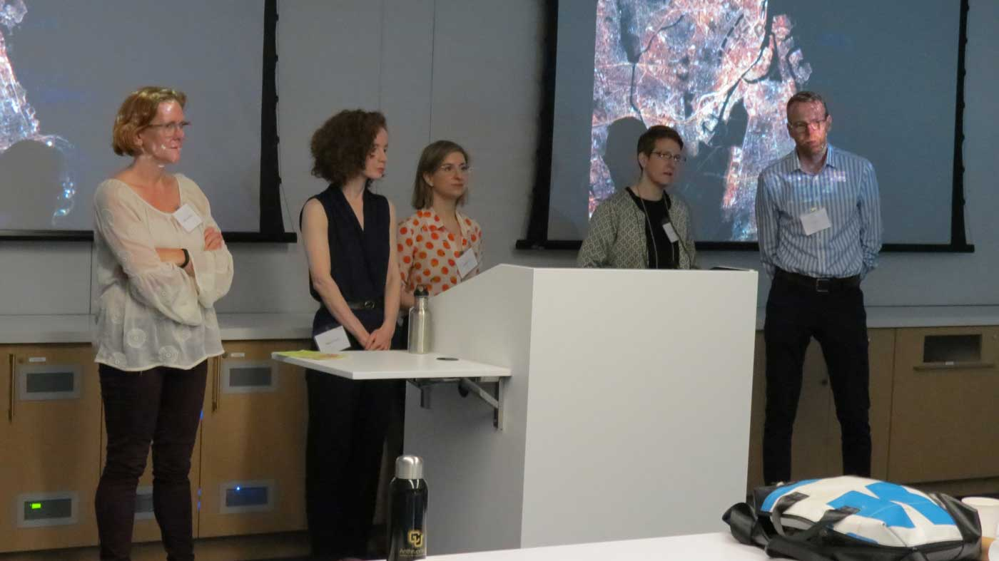 five speakers stand in front of a podium speaking to the audience