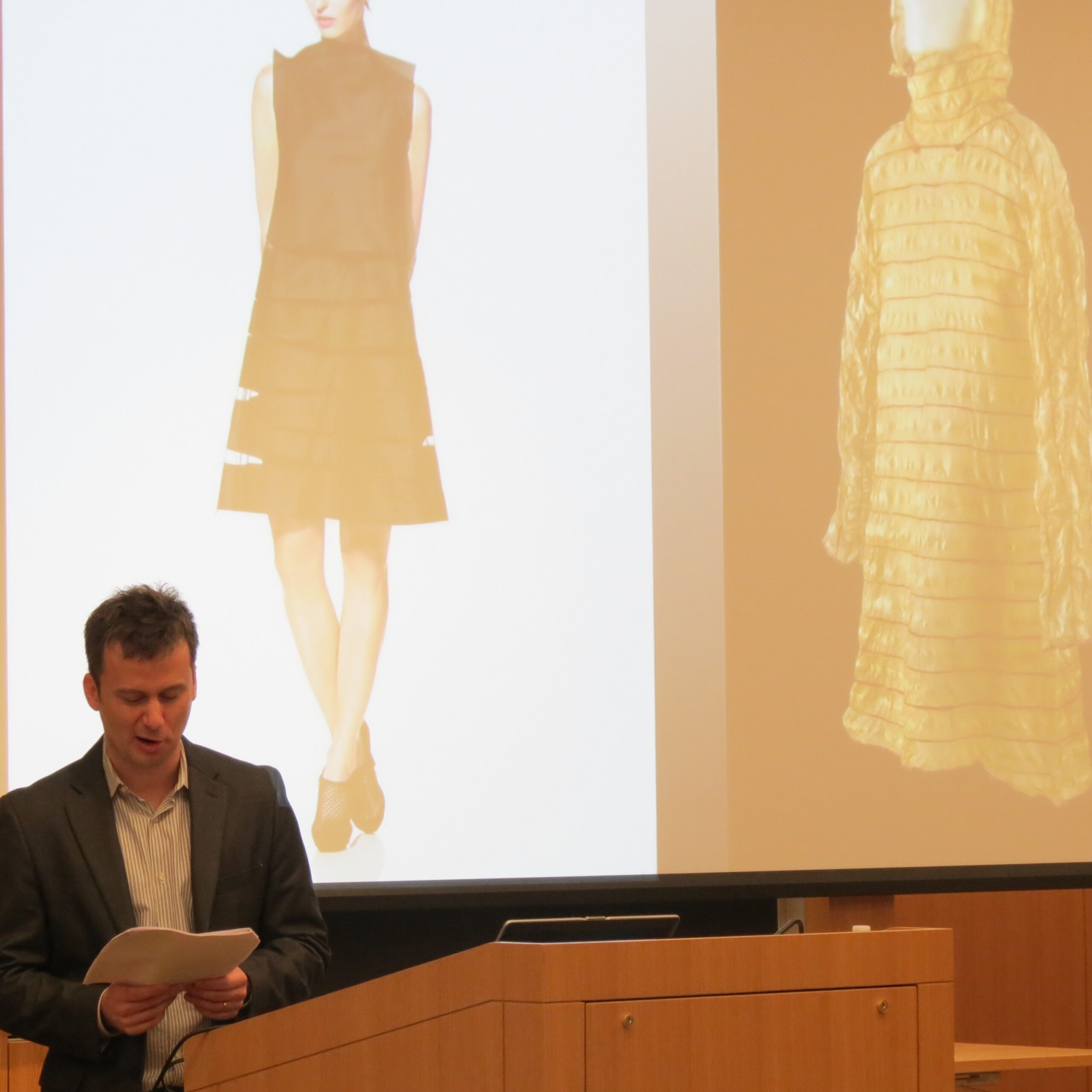 speaker reading aloud in front of slide of two dresses on mannequins