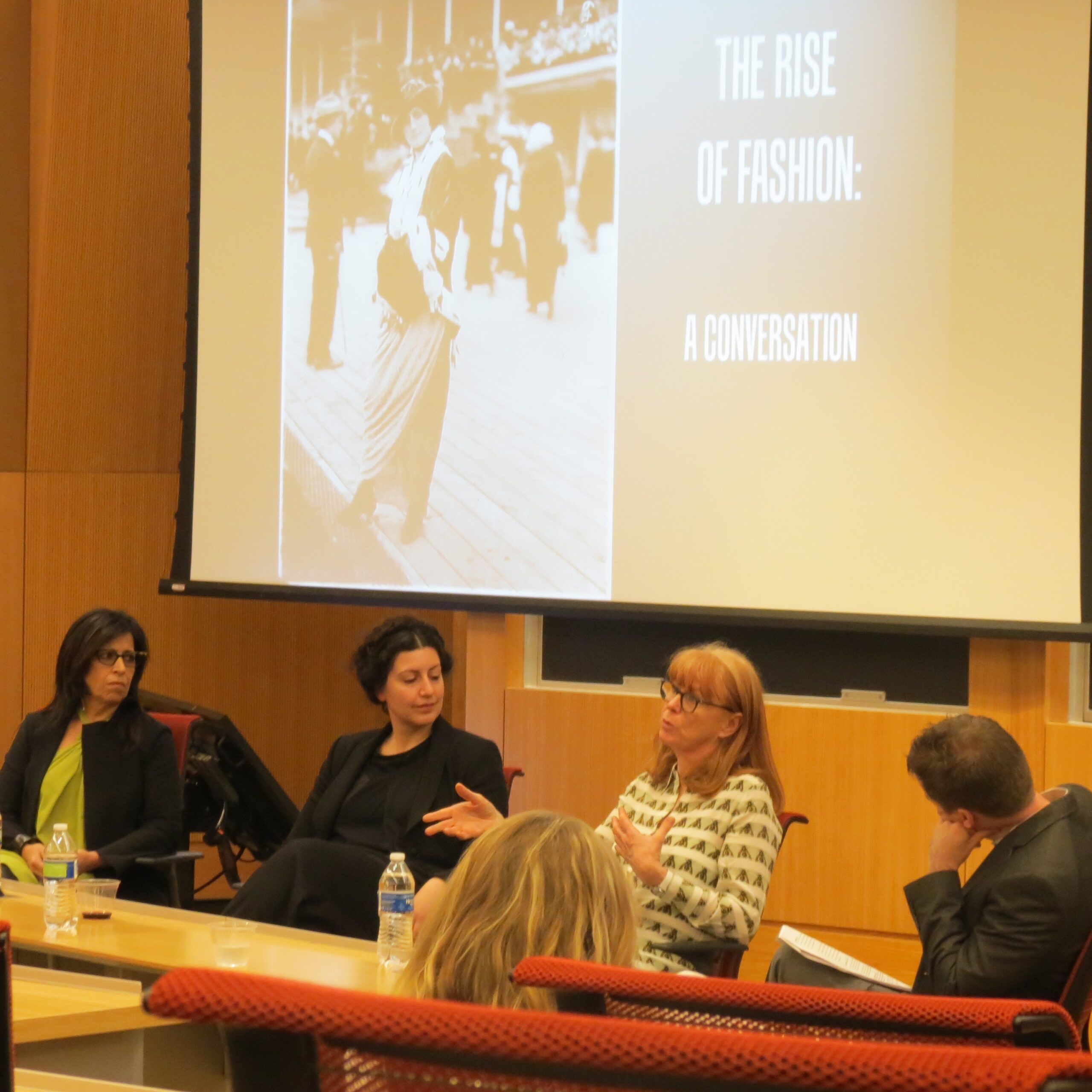 four panelists in conversation with audience in foreground