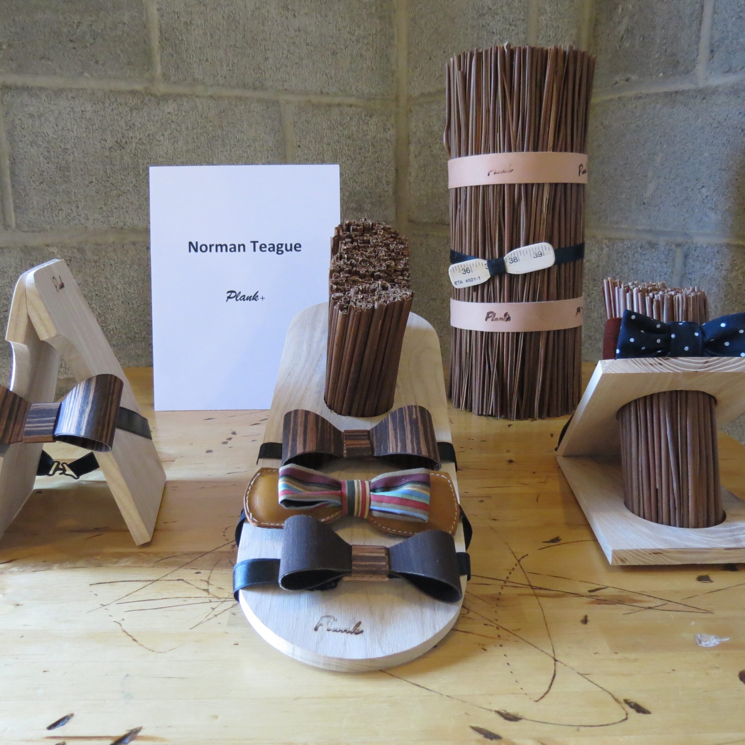 a display of wooden, leather, and fabric bowties by Norman Teague, Plank+