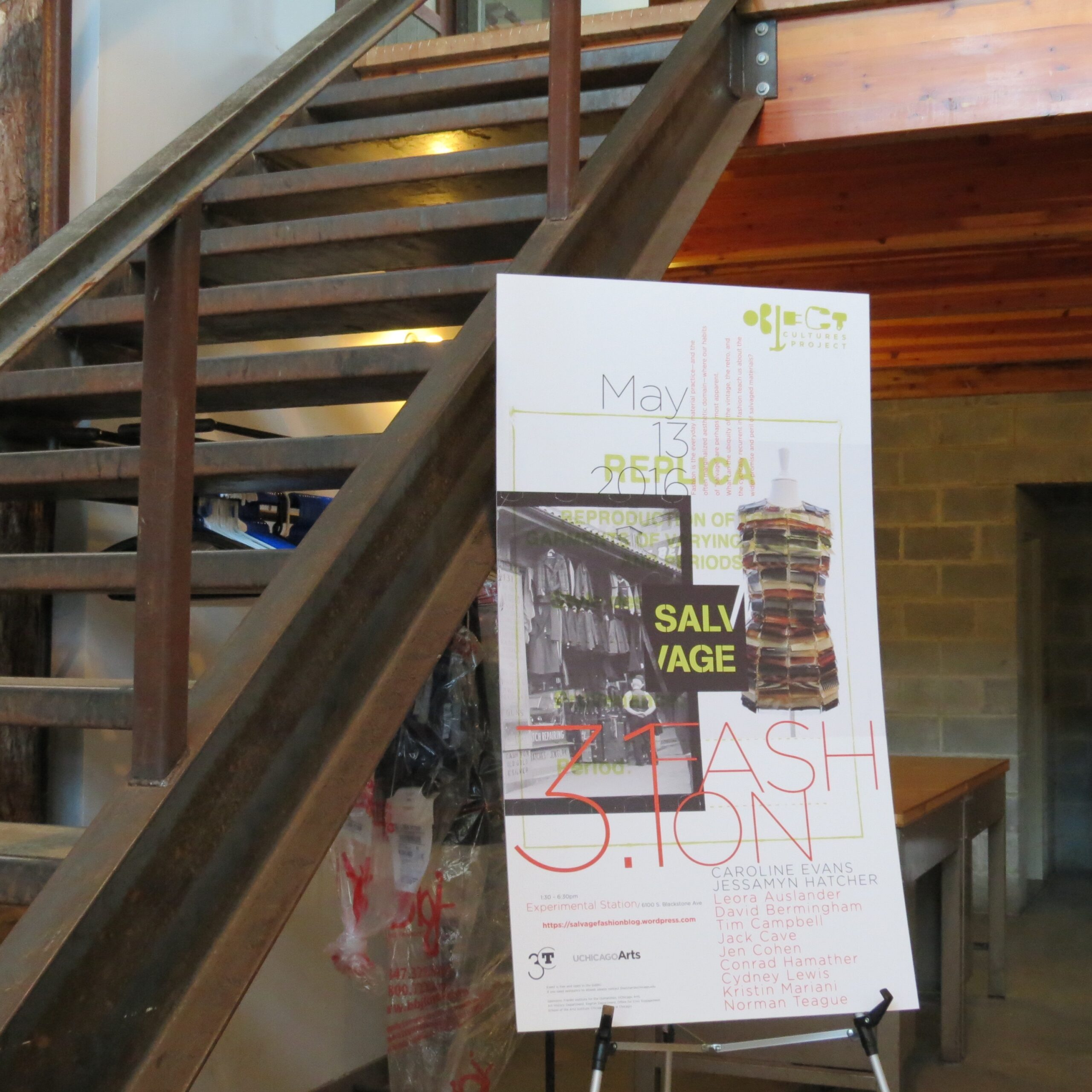 Photo of Salvage 3.1 poster in front of modern wooden staircase