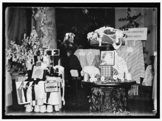 a display of clothing materials and antique furniture