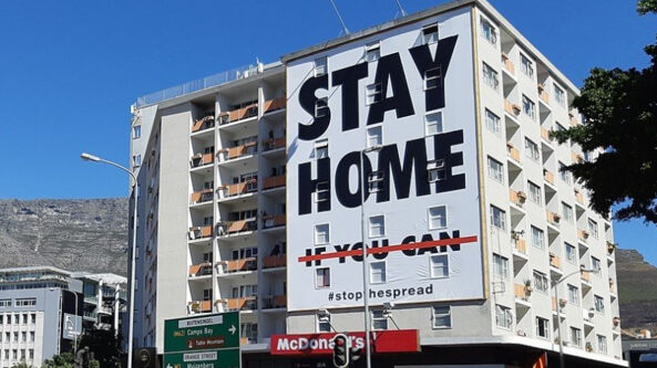 """Building with poster that reads """"Stay Home if you can"""""""