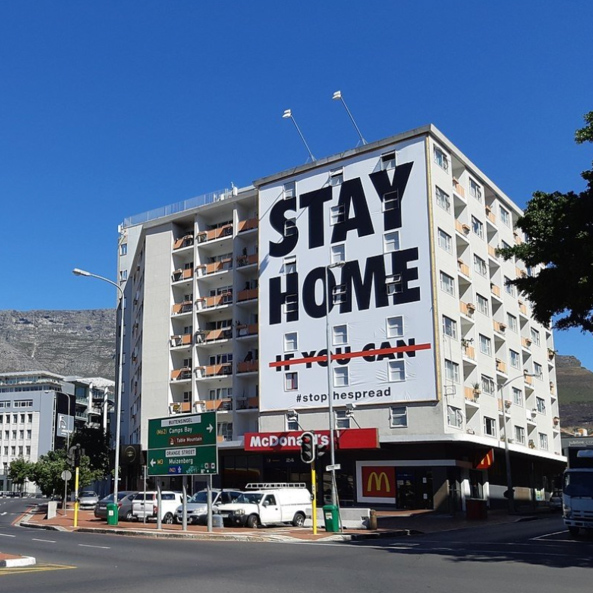 "Building with poster that reads ""Stay Home if you can"""