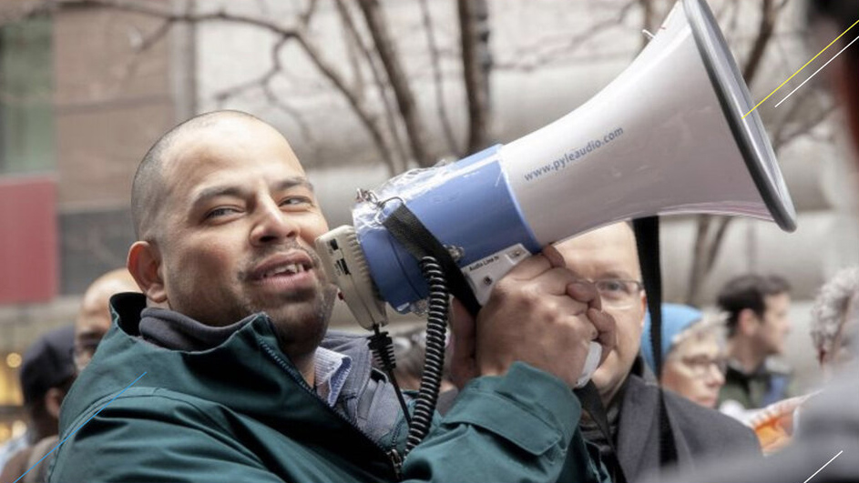 Man standing in a crowd outdoors holding a megaphone