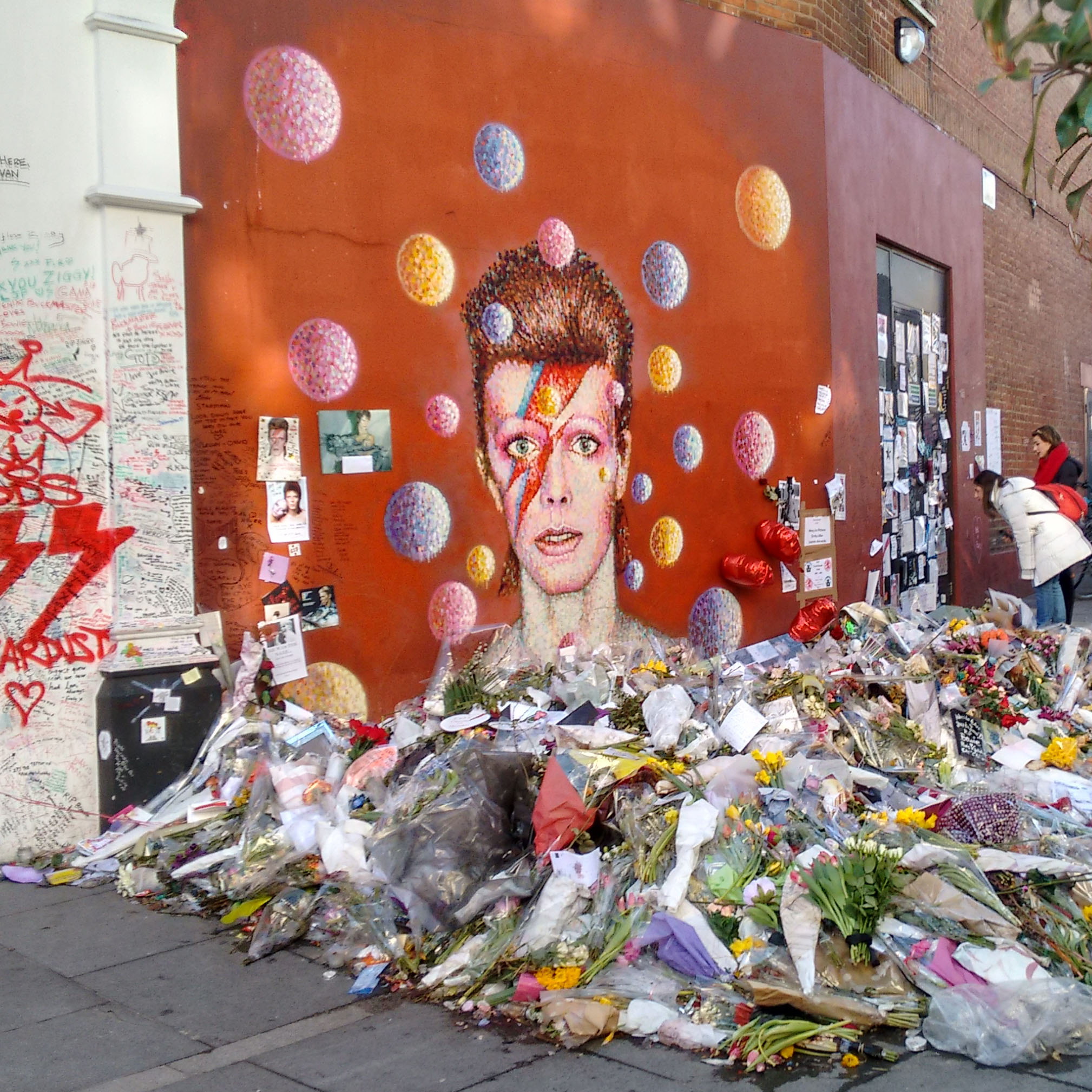 wall mural of David Bowie with pile of flower bouquets on the ground in front of it