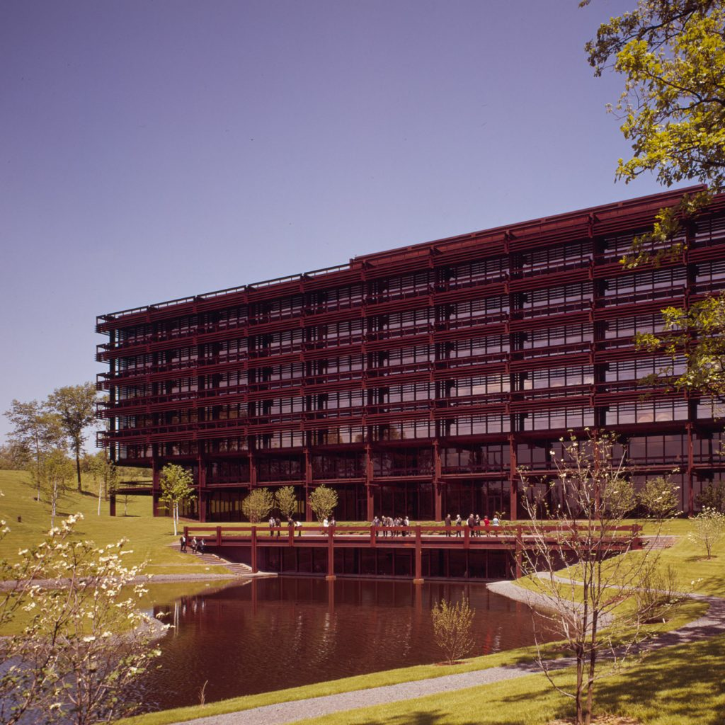 photo of office building surrounded by lake and trees