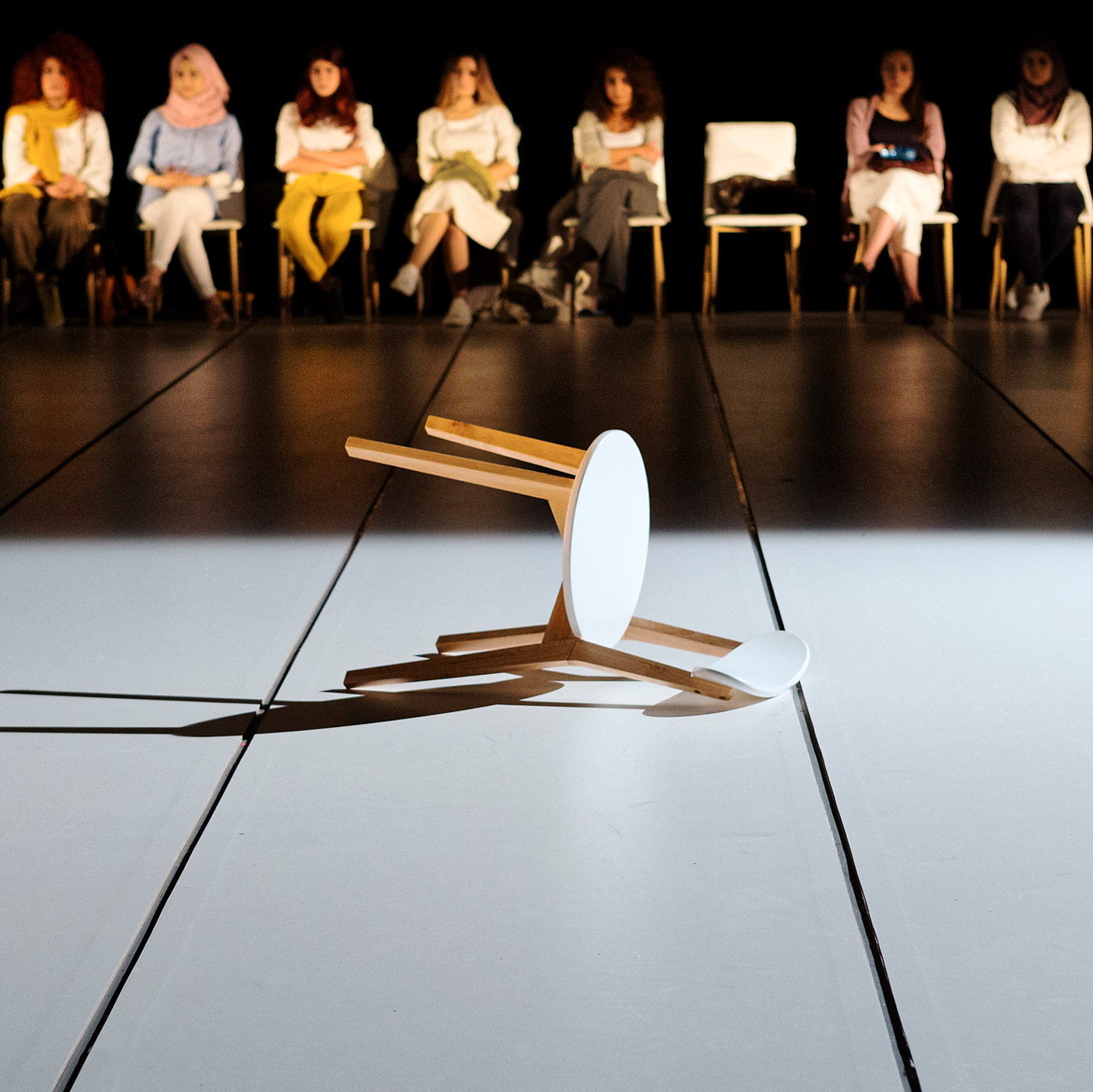 a row of people sit on chairs at rear of stage on which a chair lays on its side