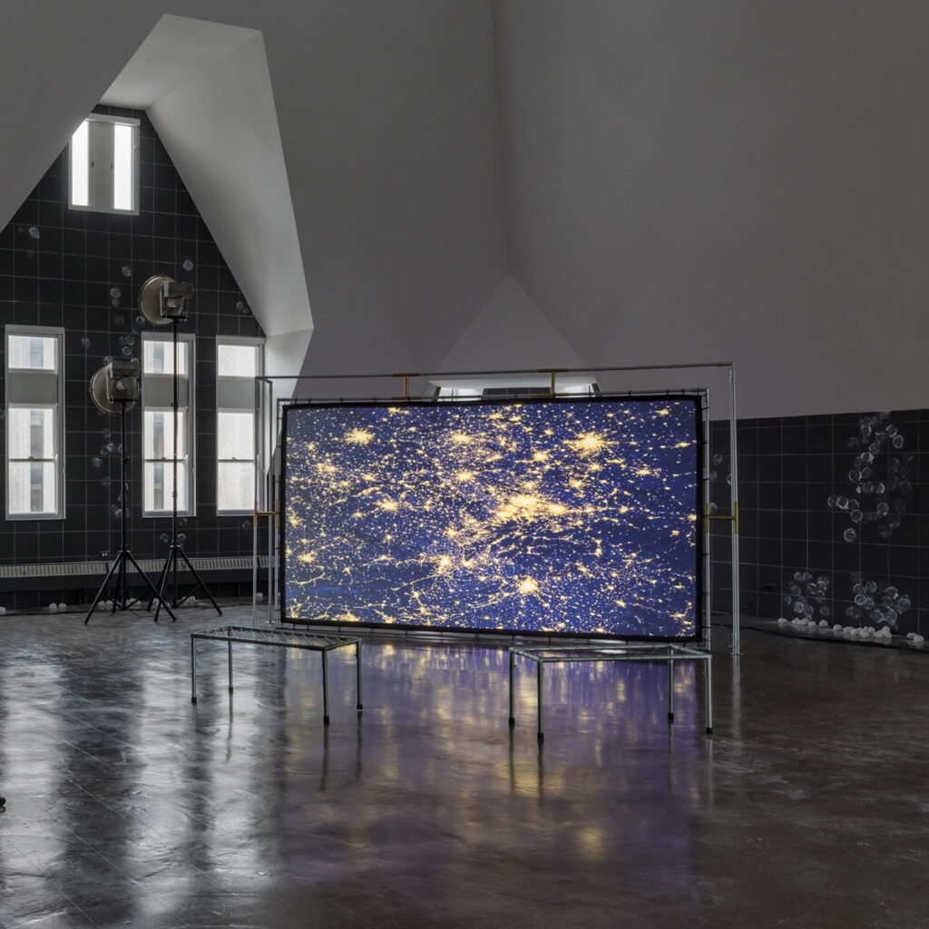 a large screen with birds-eye view of city lights sits within a large gallery space