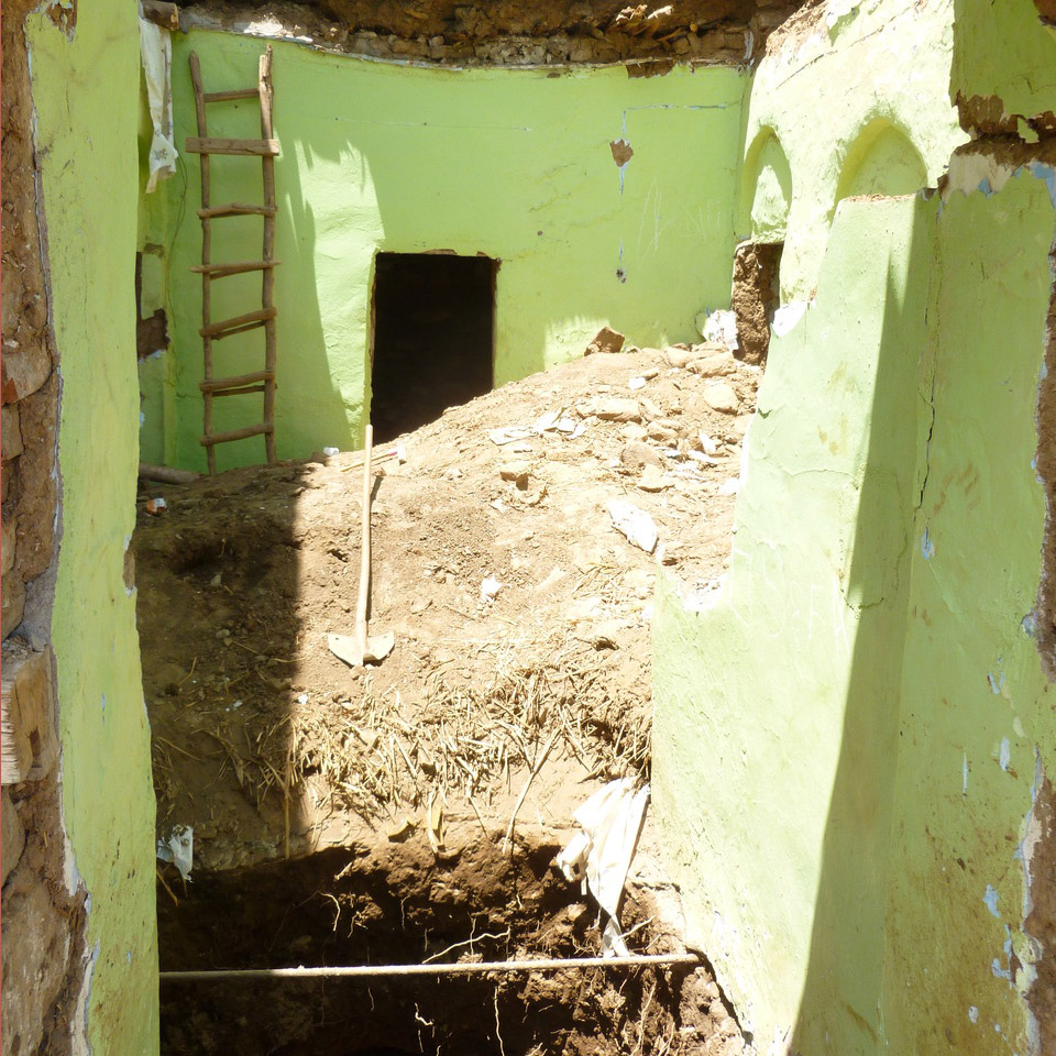 a shovel lays on top of a pile of dirt in front of a hole, surrounded by pale green walls